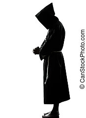 man monk priest silhouette praying - one caucasian man...