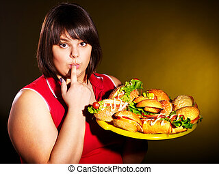 Woman eating hamburger. - Overweight woman eating hamburger.