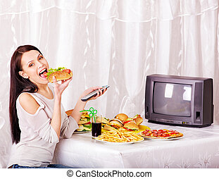 Woman eating fast food and watching TV.