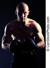powerful - Portrait of an aggressive boxer in gloves posing...