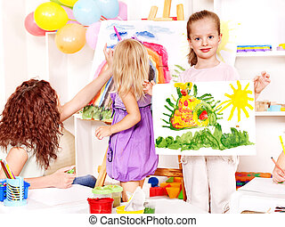 Child painting at easel. - Child painting at easel in...