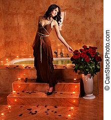 Woman relaxing in bath. - Woman sitting on edge of sauna.
