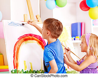 Child painting at easel - Two child painting at easel in...