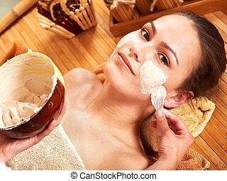 Young woman having clay facial mask. - Beautiful girl having...