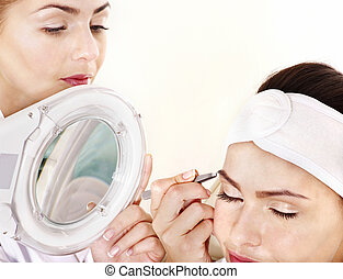 Tweezing eyebrow by beautician Isolated