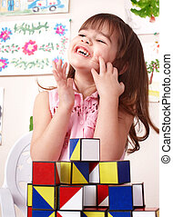 Child playing  block in play room. Preschool.