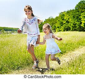 Kids running across green grass outdoor. - Group children...