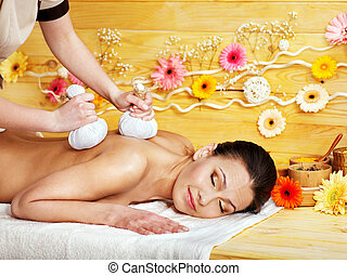 Woman getting herbal ball massage. - Woman getting herbal...