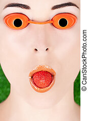 Detail portrait of a woman wearing tanning bed glasses with strawberry in mouth against green
