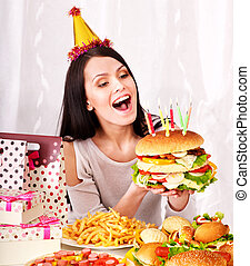 Woman eating hamburger at birthday.