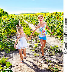 Children running across sunflower field outdoor. - Group...