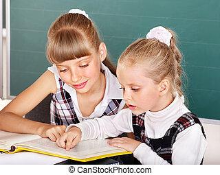 Schoolchildren in classroom near blackboard.