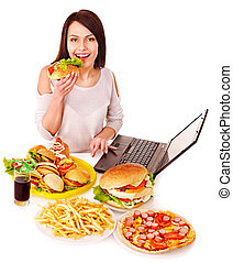 Woman eating junk food - Woman eating fast food at work...