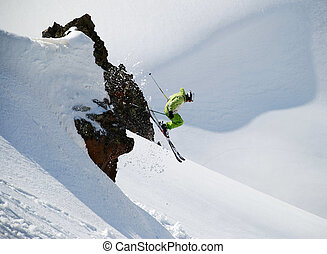 Skier jumping from a cliff - Skier in a green suit, jumping...