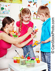 Children painting with teacher . - Children painting with...