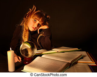 "Child reading magic book at candle. ""Fortune telling"""