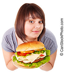 Woman eating hamburger - Overweight woman eating hamburger...