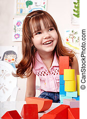 Child with block and construction set in play room. - Child...