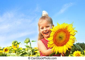 Child holding sunflower outdoor.