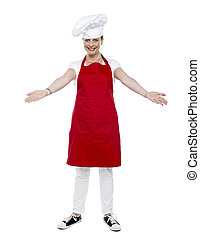 Full length portrait of chef posing in uniform with her arms...