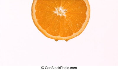 Drop of orange juice in super slow motion falling against a...
