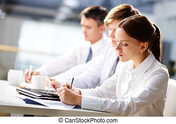 Seminar notes - Group of business people taking notes at...
