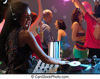 woman dj entertaining crowd in night club - sexy, young...
