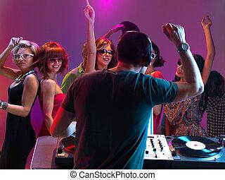 dj playing music in night club - sexy, young women dancing...