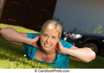 gymnastic exercise - Blonde woman lying on a lawn and makes...