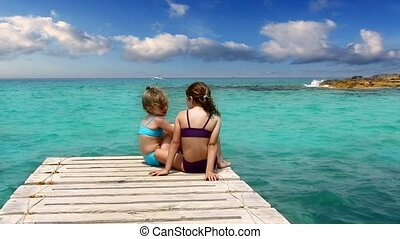 little sisters girls looking beach