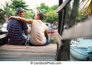 Old man and boy fishing together on river for fun - People...