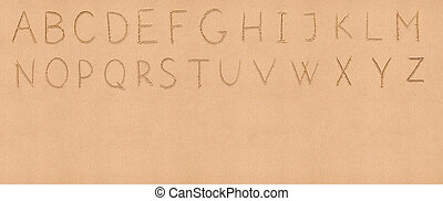 Handwriting English alphabet on flat sand with empty space...