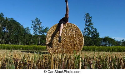 hay bale fun - funny man and Hay bale on a summer afternoon