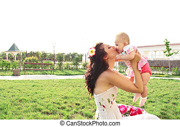 Mother kissing her baby at outdoors