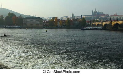 Pleasure boats move on vltava river in Prague autumn sunset
