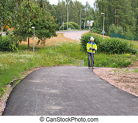 Engineer aligning the road with a theodolite tool