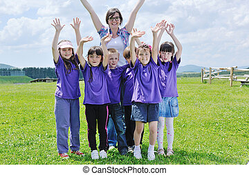 happy kids group with teacher in nature