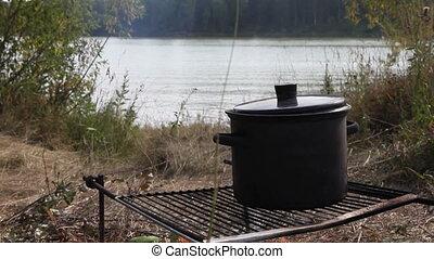 Pot on fire near Siberian river, 2 cuted shots in 1: medium...