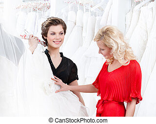 Two girls have a good look at the wedding dress preparing to...