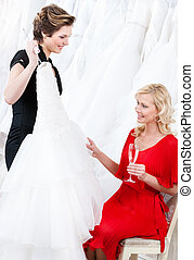 Shop assistant proposes a wedding dress to the bride