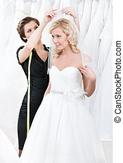 Shop assistant helps to fix the wedding veil - Shop...