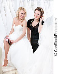 Future bride in wedding gown puts the garter on