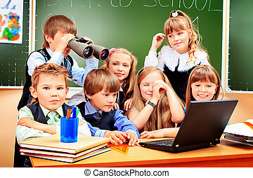 classmates - Happy schoolchildren at a classroom looking...