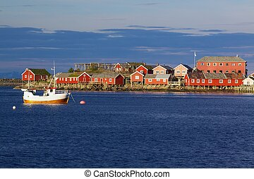 Lofoten islands - Red fishing rorbu huts and fishing boat in...