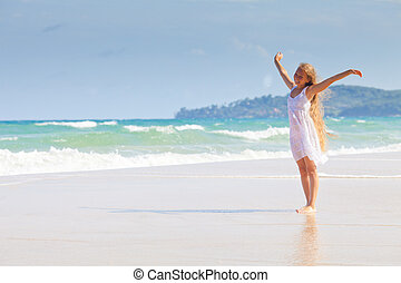 Happy girl with long hair in white dress on sea beach