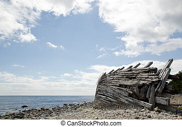 Old wooden shipwreck by a stony coast