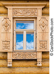 Wooden decorated window in log house, Russian traditional...