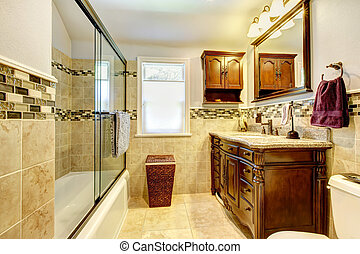 Nice bathroom with natural stone tiles and wood cabinet. -...