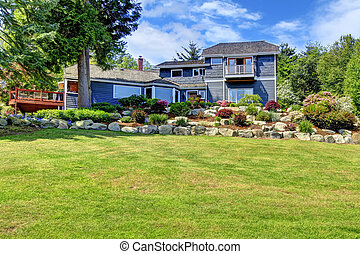 Large blue house on the hill with green land. - Large blue...