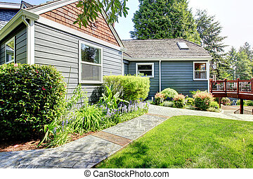 Grey house with deck and green landscape. - Grey house side...